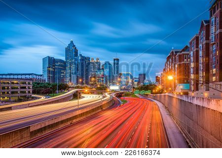 Atlanta, Georgia, USA downtown skyline and highway at dusk.