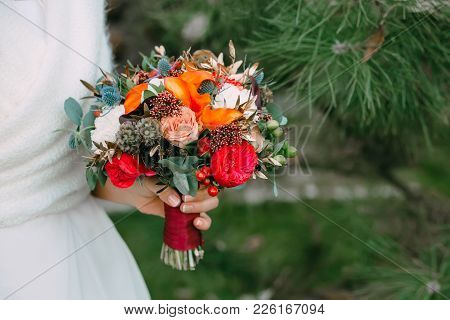 Bride Holds A Wedding Bouquet. Wedding Bouquet Of Red And Cream Roses On Green Background. Top View.