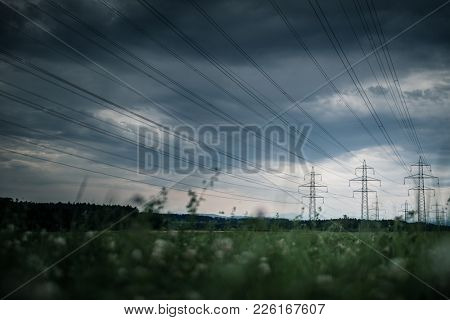 High-voltage power lines. electricity distribution station . high voltage electric transmission tower in landscape (shallow DOF with out of focus grass in the foreground)
