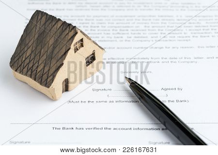 House Or Real Estate Buy And Sell Mortgage Concept, Miniature House On Printed Paper Document And Pe