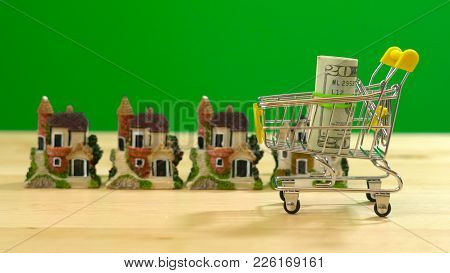 E-commerce Retail Estate Shopping For Houses Concept With Miniature Shopping Cart Against Chroma Key