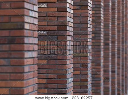 Perspective Diagonal View On Abstract Brown Red Brick Wall With Columns With Blurred Background. Arc