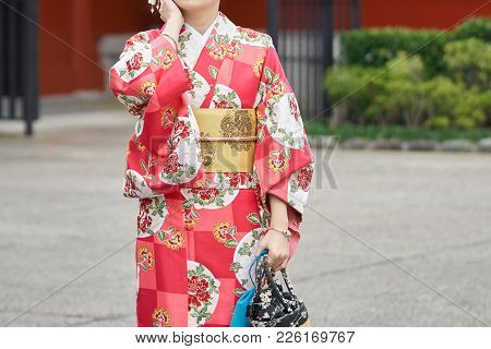 Young Girl Wearing Japanese Kimono Standing In Front Of Sensoji Temple In Tokyo, Japan. Kimono Is A