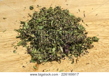 Pile Of Crushed Dried Thyme To Spice Up Dishes Closeup On Wooden Board Background