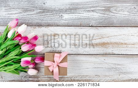 Overhead View Of A Springtime Pink Tulips And Brown Gift Box On White Weathered Wooden Boards