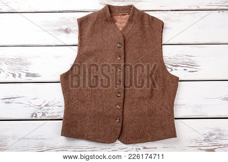Women Sleeveless Warm Garment. Female Brown Color Classic Vest On White Wooden Background. Boutique