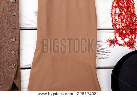 Female Classic Clothes And Accessories Background. Women Skirt, Vest, Necklace And Black Hat. Classy