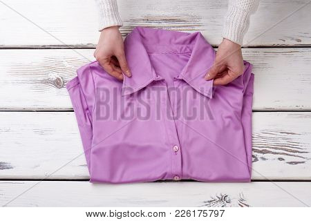 Female Hands And Blouse, Wooden Background. Woman Folding Clothes. Female Formal Outfit On Sale.