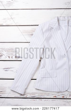 Female White Formal Blazer. Women Cotton Striped Jacket On White Wooden Background, Cropped Image.