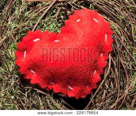 A Single Red Cloth Heart On A Green Mossy Background