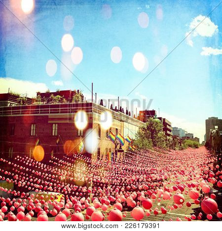 Joyful Summer Street In Gay Neighborhood Decorated With Pink Balls, With Bokeh Light Effect. Annual