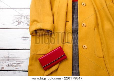 Female Cashmere Overcoat Of Yellow Color. Women Classy Topcoat And Red Purse On Wooden Background Cl