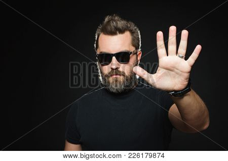 Serious Man With Beard In A Black Shirt And Sunglasses On A Black Background In Studio. Confident Gu