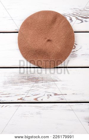 Female Wool Beret, Copy Space. Women Headgear On White Wooden Table, Space For Text. Feminine Classi