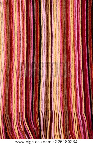 Striped Multicolored Scarf Close Up. Knitting Texture Of Colored Knitted Fabric. Detail Of Female Wi