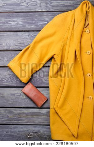Female Luxury Yellow Overcoat. Women Fashion Cashmere Topcoat And Leather Purse On Old Wooden Backgr