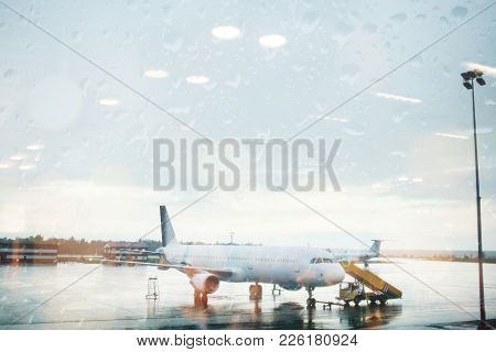 Plane Picks Up Passengers In The Rain. Disadvantageous Of A Cloudy Day To Fly. View Through Glass.