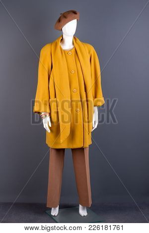 Female Mannequin In Fashion Style Garment. Mannequin Wearing Beautiful Overcoat, Brown Beret And Tro
