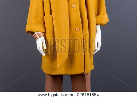 Female Mannequin In Yellow Topcoat. Mannequin Wearing Fashionable Jewelry, Grey Background. Women Br
