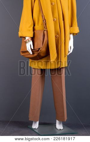 Women Stylish Handbag And Trousers. Female Mannequin Clothed In Elegant Topcoat And Trousers. Femini