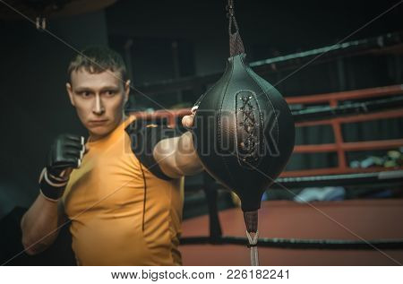 Active Man In A Gloves Beats A Punching Bag In A Gym.