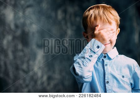 Five year old boy covered his eyes with his hand. Childhood. Children's games.