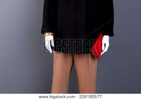 Female Mannequin With Red Lacquered Purse. Dummy In Black Coat With Fashion Bracelets And Wallet. Wo