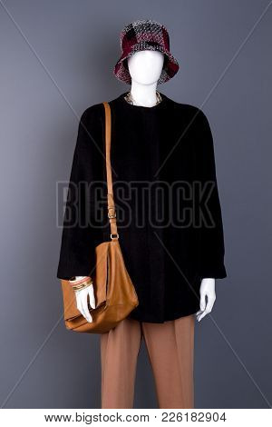 Fenale Cute Hat On Mannequin. Female Mannequin With Modern Coat And Handbag, Grey Background. Femini
