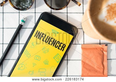 Top View Influencer Feature On Mobile Screen With Coffee Cup,sunglasses,pencil On White Table Cloth.