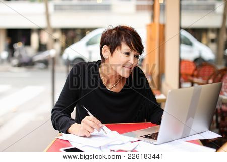 Aged Teacher Sitting On Veranda And Checking Student S Test Using Laptop But Woman Take Pause For Wr