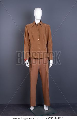 Mannequin In Women Brown Suit. Female Casual Attire On Dummy, Grey Background. Feminine Office Outfi