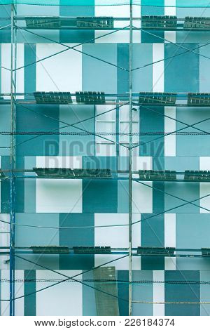 Building Facade Under Renovation With Protective Mesh And Scaffolding