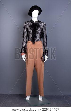 Female Black Hat And Blouse On Mannequin. Dummy With Brown Trousers, Black Blouse And Purse. Ladies