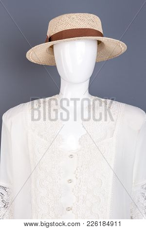 Mannequin In Feminine Classy Clothes. Straw Hat With Ribbon And White Lace Blouse On Mannequin, Grey