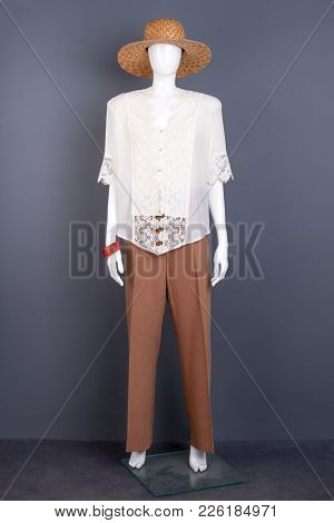 Full Length Mannequin In Straw Hat. Female Mannequin Dressed In Woven Hat, Lace Blouse And Brown Tro