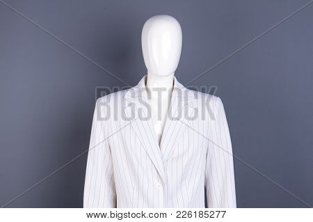 Female Mannequin In White Striped Blazer. Business Style Women Jacket On Dummy, Grey Background.