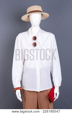 Straw Hat, White Blouse And Fashion Accessories. Female Mannequin With White Blouse, Brown Trousers