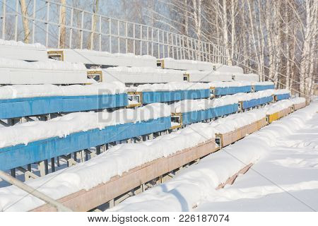 Seats In The Stadium Under The Snow. Chairs For Spectators At The Stadium Under The Snow.