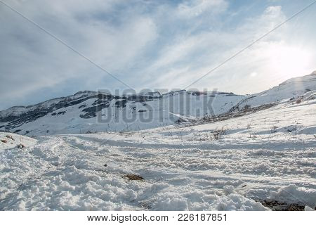 Panoramic View Of Mountain Winter Landscape With Snowy Peak. Dramatic Clody Sky.