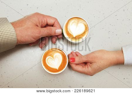 hands of lovers which hold cups of coffee