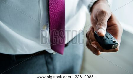 A man signalling his car with a remote controller