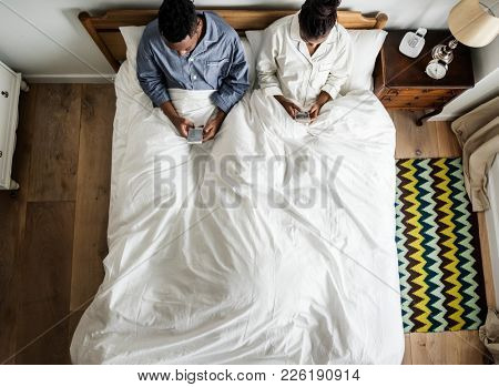 African American couple on bed using cellphones