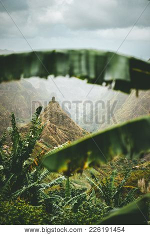 Mountain Peak Of Xo-xo Valley Visible Throught The Banana Leaves Frame Down The Valley. One Of The B