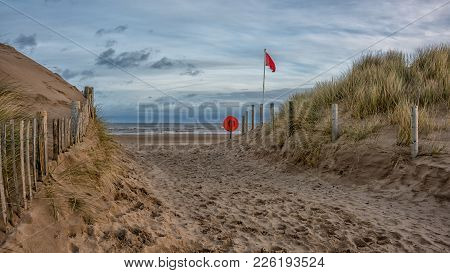 A View Of The Deserted Beach With A Path Through The Sand Dunes Showing The Lifebuoy And The Red Fla