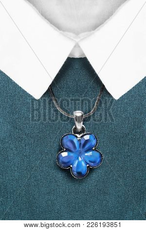 Blue Crystals Flower Pendant On A Chain Over Blue Pullover With White Collar