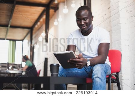 Smiling African Man Using Tablet For Video Conversation In Modern Office. Concept Of Young Business