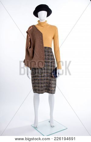 Female Mannequin In Casual Outfit. Women Black Hat, Sweater, Skirt And Brown Waistcoat On Shoulder.