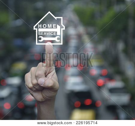Hand Pressing Hammer And Wrench With House Icon Over Blur Of Rush Hour With Cars And Road, Home Serv