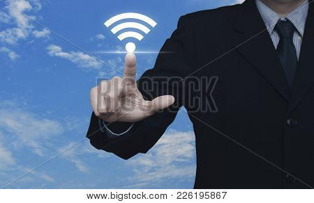 Businessman Pointing To Wi-fi Button Over Blue Sky With White Clouds, Technology And Internet Concep