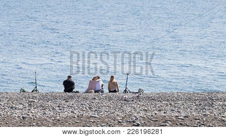 Sochi - April 3, 2017: Two Young Girls And Two Young Men Rest On The Pebble Beach Of The Black Sea A